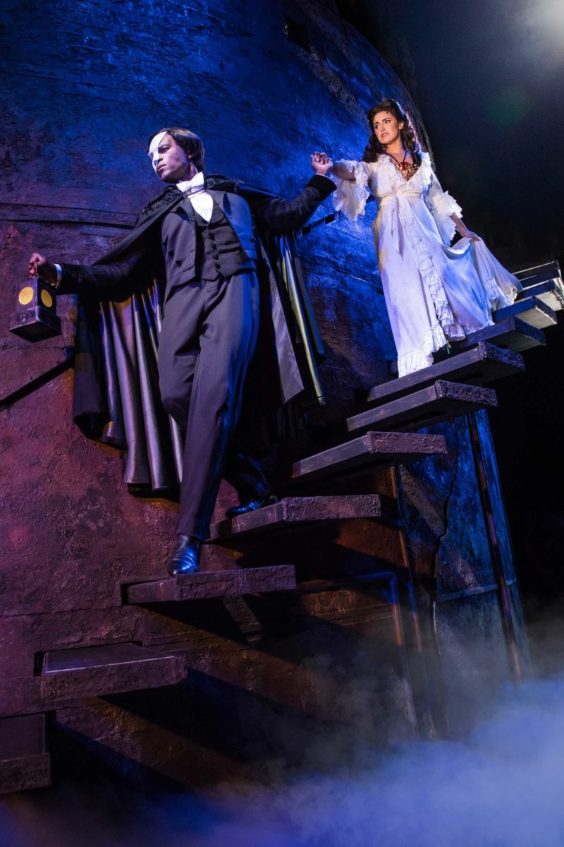 The Phantom of the Opera leads Christine down a dark staircase into the depths of the Paris Opera House to his lair.
