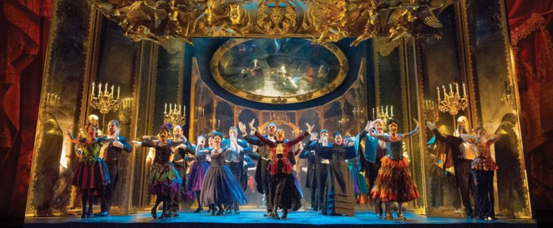 The entire company dances in a hall of mirrors dressed in their costumes and masks for a masquerade gala at the Paris Opera House.