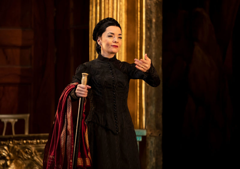 The ballet mistress, Madame Giry, stands with her arm outstretched in invitation as she provides instruction during a dress rehearsal of the upcoming opera, Hannibal.